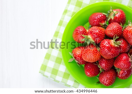 Plate with fresh strawberries on green and white checkered napkin.Top view.
