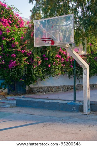 playground with a basketball ring, surrounded by flowers - stock photo