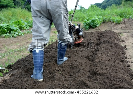 plow the field with a farm tractor - stock photo