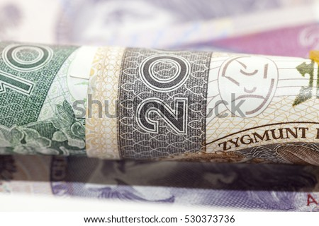 Polish banknotes photographed close-up. Shown details of bills. International designation - PLN. Money rolled into a tube