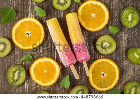 Popsicles with sliced orange and kiwi fruit on wooden background. Top-view. - stock photo