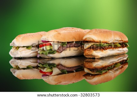 3 popular sandwiches - Chicken Caesar, Deli giant and Philly on green - stock photo