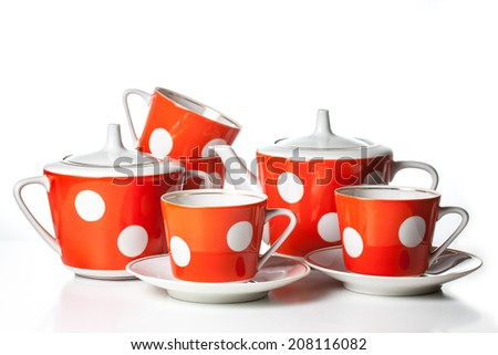 Porcelain dishes for Tea Time. Tea set on white background, red and  white polka dots.  Teapot, sugar bowl,  four tea cups  with saucers.  Set for coffee, nice tableware. - stock photo