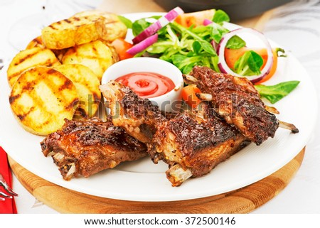 Pork Ribs and Fried Potato Wedges on White Plate with Sauce and Veggies - stock photo