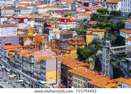 PORTO, PORTUGAL, on June 17, 2017. The sun lights an attractive architectural complex of Douro River Embankment of in downtown. Cars are parked on the embankment. View from Ponte Luis I Bridge
