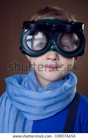 Portrait  a young boy. He is wearing blue scarf  and welding glasses on brown background. Studio shot - stock photo