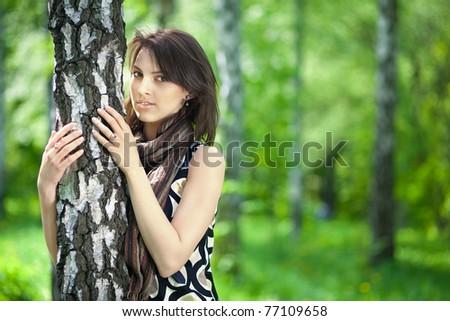 .Portrait of a beautiful young woman embracing a birch tree, European, White, Caucasian - stock photo