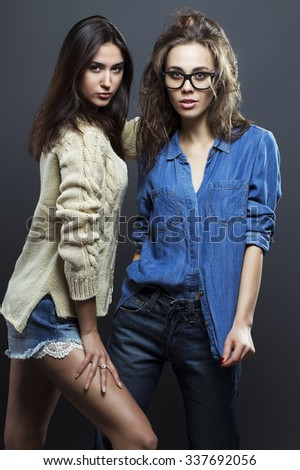 Portrait of a gorgeous brunette fashion women in casual shirt, jeans, knitted sweater, wearing in trendy glasses posing on gray background. Perfect skin and hairdo. Vogue style.  Studio shot.