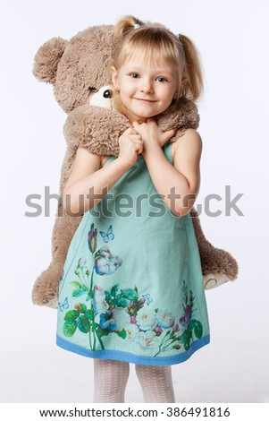 Portrait of a little blonde girl hugging a teddy bear toy - stock photo