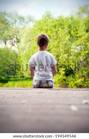 Portrait of a little boy in the forest - stock photo