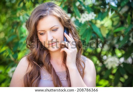portrait of a smiling beautiful woman talking on the phone  - stock photo