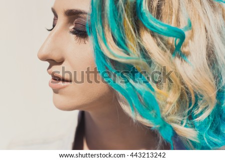 Portrait of a young beautiful bright girl hipster closeup with blue green hair with smokey ice outdoors on a sunny day in the street lifestyle in denim jacket smiling and posing
