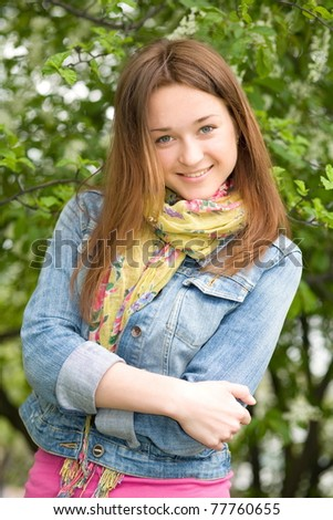 Portrait of a young girl against the backdrop of flowering trees.