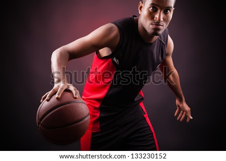 Portrait of a young male basketball player against black background