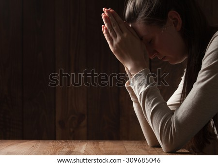 portrait of a young woman praying - stock photo
