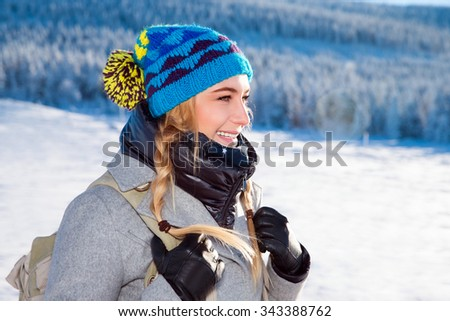 Portrait of beautiful cheerful girl in the mountains covered with snow, enjoying winter travel to Alps, Europe