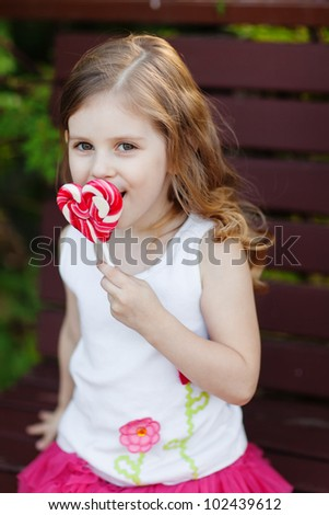 Portrait of beautiful curly girl with heart lollipop
