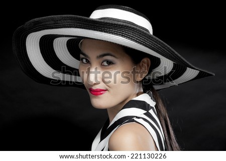 portrait of beautiful sexy young woman with red lips on black background with hat - stock photo