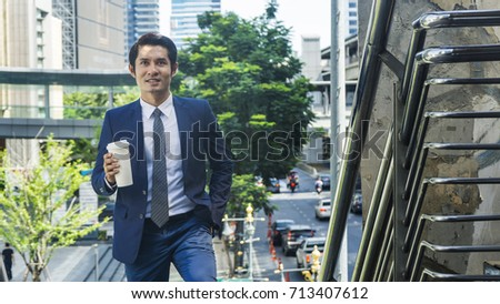 portrait of business asia man stand with paper cup of drink at outdoor pedestrian stair walkway