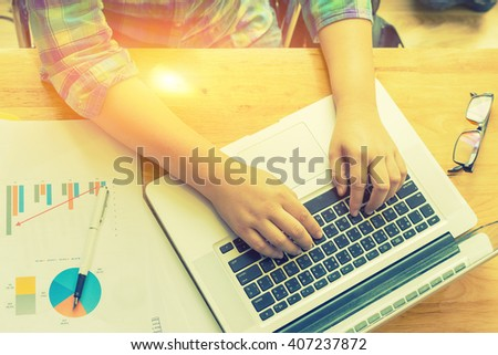 Portrait of businessman working on a laptop at office desk with paperwork and other objects,man sitting at a table with a cup of coffee,mobile phone,laptop.top view,selective focus,vintage color - stock photo