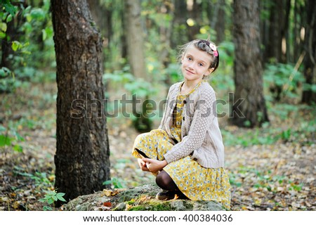 Portrait of cute child girl in glasses having fun in autumn park wearing casual dress, knitted sweater and boots