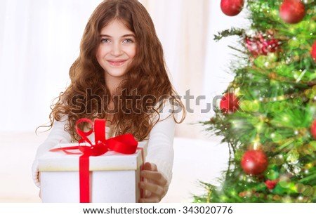 Portrait of cute happy teen girl with gift box standing near beautiful decorated Christmas tree, with pleasure celebrating winter holidays - stock photo