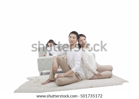 Portrait of daughter leaning sofa,parents sitting on carpet,back to back