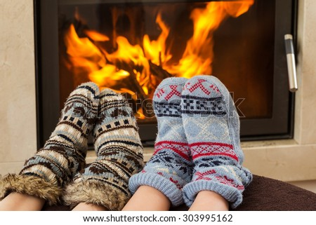 portrait of feet at woolen socks warming at fireplace in winter  - stock photo