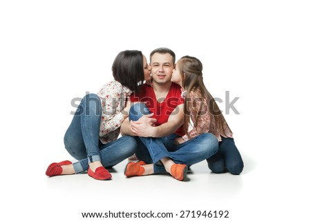 Portrait of happy and friendly family. Pretty little daughter, beautiful wife and mother kissing their father and husband  - stock photo