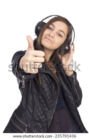 Portrait of happy cute  teenage girl  with headphones listening music and showing thumb up isolated on white background - stock photo