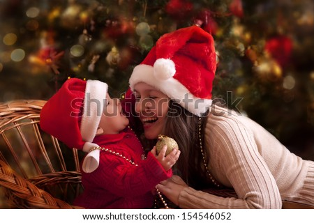 Portrait of happy mother and litlle baby in santa's hats - stock photo