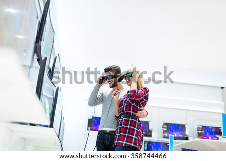 Portrait of happy young couple in electronics store trying a new TV. - stock photo