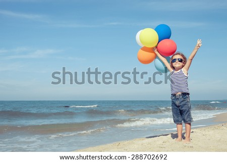 Portrait of little boy with balloons standing on the beach at the day time  - stock photo