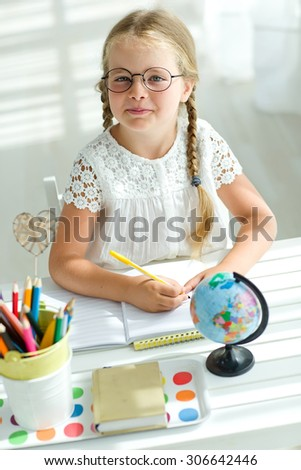 Portrait of lovely girl looking at camera while drawing - stock photo