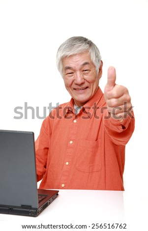 portrait of senior Japanese man with thumbs up gesture - stock photo
