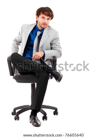 Portrait of smart young male executive sitting on chair isolated on white - stock photo