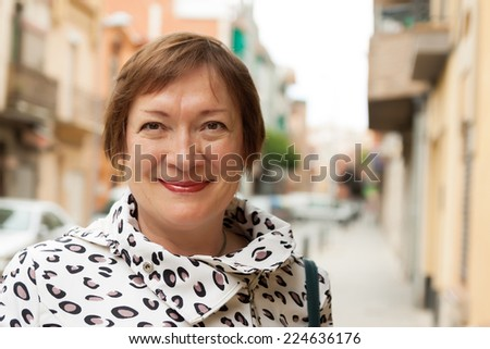 portrait of smiling mature woman at european town street - stock photo