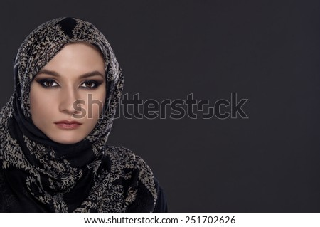 portrait of young beautiful muslim woman with head scarf isolated on gray background - stock photo