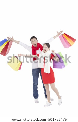 Portrait of young couple holding shopping bags