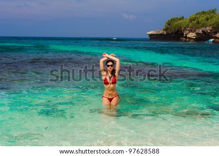 Portrait of young woman posing on beach in sunglasses - stock photo