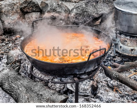 pot on outdoor fire with cooking soup - stock photo