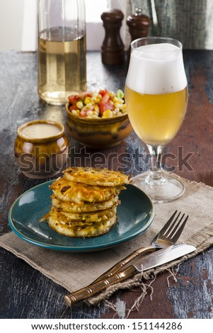potato fritters with beer set on the old rustic table - stock photo