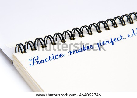 """Practice makes perfect"" calligraphic label written on a white open notebook page, closeup"