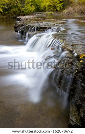 Prairie Creek flows over a waterfall before emptying into the Kankakee River in Will County, Illinois. - stock photo
