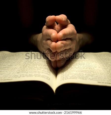 prayer over a  Bible - stock photo