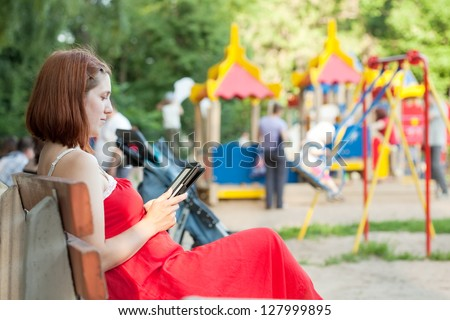 pregnancy woman reads e-book against  playground area