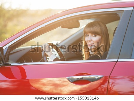 Pretty girl in a car at sunset - stock photo