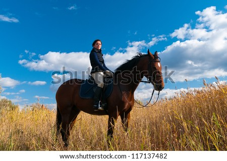 Pretty girl riding horse and look at view front of reed - stock photo