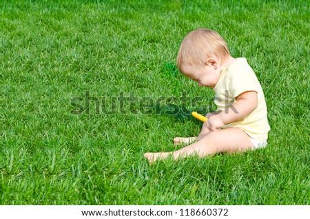 ? pretty little boy sneezes sitting on a grass - stock photo