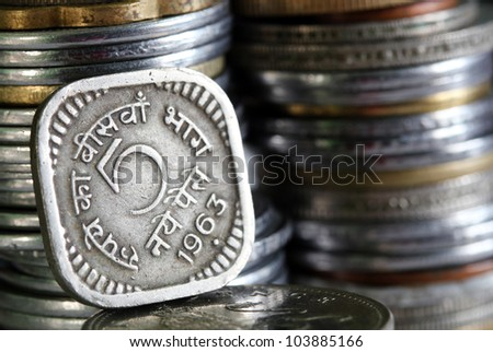 1963 printed 5 Paisa indian currency coin with stack of other coins in the background